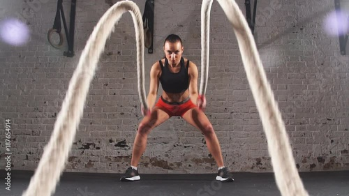 Poster Athletic young woman doing some crossfit exercises with a rope indoor. Slow motion