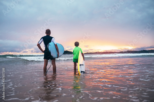 Foto op Canvas Snelle auto s Father and son stand on the surf line with surf boards on sunset