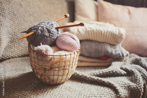Fotobehang Bol Grey and pink Yarn ball with knitting needles in metallic basket with knitted sweaters on background. Hobby, cozy homely weekend and hugge concept.