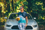 Young man standing by the Ford Mustang GT on the island of Kauai, Hawaii holding a coconut in his hand. August 10, 2017. USA, Hawaii.