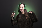 Portrait of a young girl listening music with green headphones