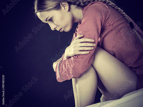 Sad depressed young woman in bed - 187683330