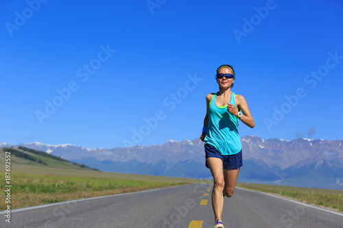 In de dag Jogging Young fitness healthy lifestyle woman runner running on road with snow capped mountains in the distance