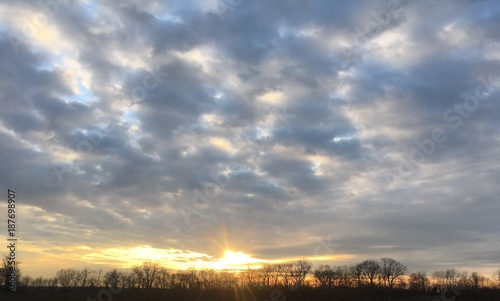 dramatic sunset with clouds over farmland
