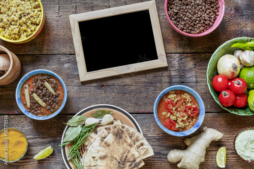 Indian cooking. In the center there is an empty frame for the text. Various vegetarian dishes made of lentils,local snacks in multi-colored bowls, top view. Concept: Authentic Indian dishes