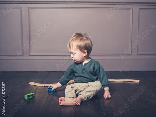 Fototapeta Cute little boy playing with wooden train