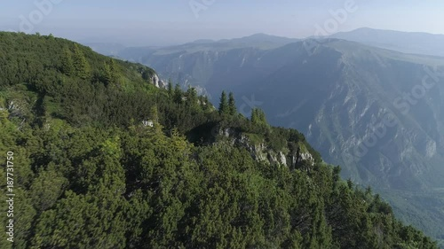 Bird's eye view of high mountains and valley covered with forest. Durmitor National Park, Montenegro. Aerial drone shot. 4K, UHD