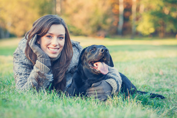 Young woman with her best friend black labrador retriever