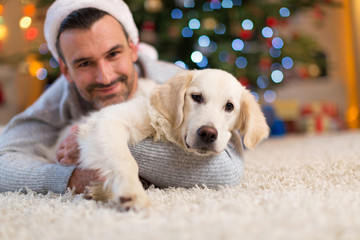 Man and dog by Christmas tree