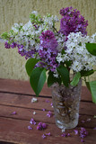 Lilac bunch in a vase on wood background. Beautiful violet and white flower still life Easter or Spring border design on wooden table. Beauty fragrant bouquet with Copy space - 187738513