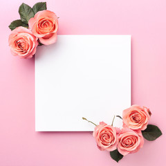 Blank paper note and roses on pink background
