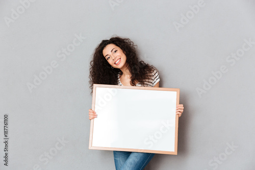 Caucasian woman with beautiful hair posing over grey wall holding piece of art in hands expressing admiration about portrait copy space
