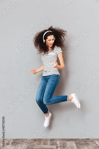 Full size view of playful female dancing and partying with waving hair against grey background while listening music in earphones - 187761301