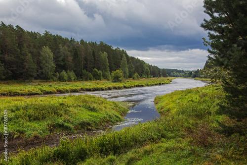 Papiers peints Rivière de la forêt River flowing gently through woodland landscape, view before a thunderstorm. Location in Russia, Tverskaya oblast