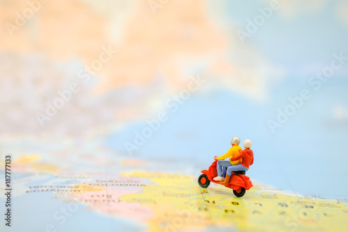 Tuinposter Scooter Travel Concept. Group of traveler miniature figures ride motorcycle / scooter on world map.