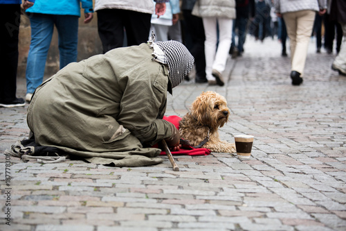 Foto op Canvas Praag A beggar with a dog on the street of a European city