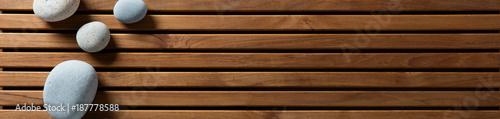 Leinwanddruck Bild zen pebbles set on design wooden board, top view banner