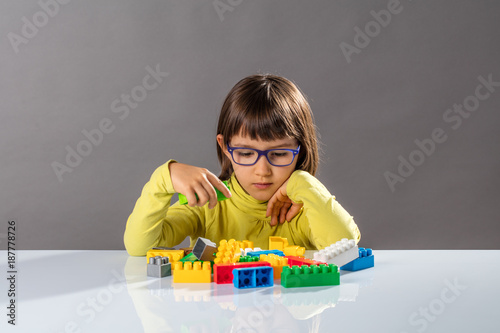 Foto Murales young child with eyeglasses thinking about organizing toys with imagination