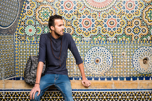 Fotobehang Marokko Young Muslim man sitting with traditional Moroccan decoration in background