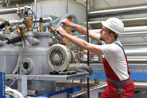 Mechaniker in Berufsbekleidung repariert Industriemaschine in einer Fabrik // Mechanic in workwear repairs industrial machine in a factory