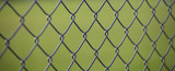 Steel wire mesh fence with green blurred background. Close up view with details.