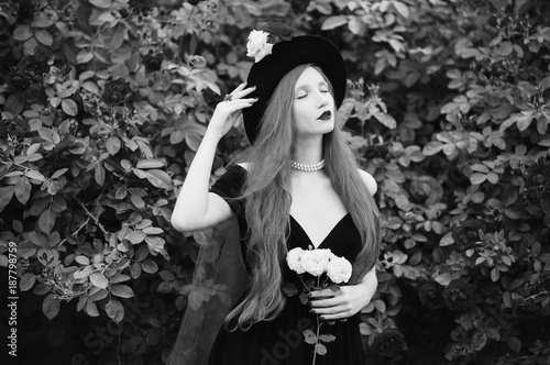 Foto Murales Redhead woman with very long hair with unusual appearance in black dress against background of red roses. Attractive girl with pale skin and bright appearance with black hat and red veil. Art photo