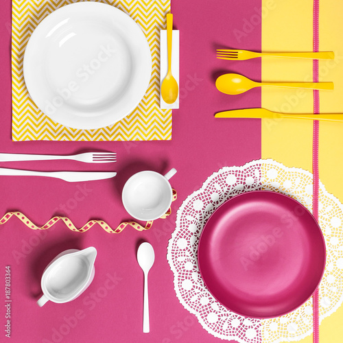 Foto Murales Serving dishes on a yellow pink background..