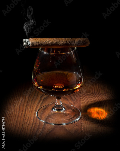 a smoky aromatic cigar and a glass of cognac
