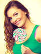 Woman charming girl with lollipop candy