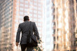 Business man walking to work, motivational conceptual perspective from behind with buildings and copy space