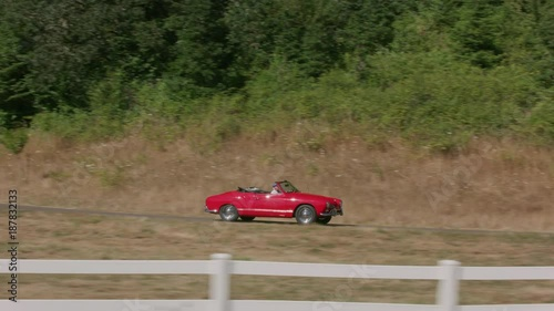 Tracking shot of man driving classic convertible car down fence lined driveway. Fully released for commercial use.