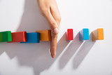 Businessperson Hand Stopping Colorful Blocks From Falling - 187847967