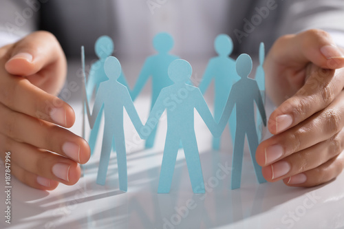 Businessperson Hand Protecting Paper Cut Out Figure On Table - 187847996