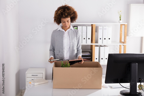 Businesswoman Packing Her Belongings In Cardboard Box