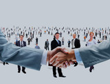 shaking hands on a background of a large group of people.