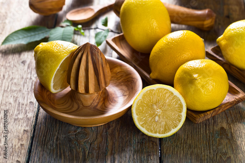 Foto Murales Lemons and old wooden squeezer .