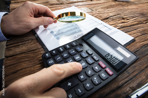 Height scale Businessman's Hand Calculating Financial Report