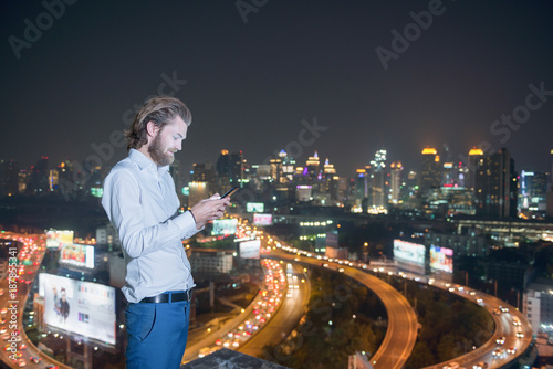 Deurstickers Bangkok Western businessman using phone with city background, technology communication concept
