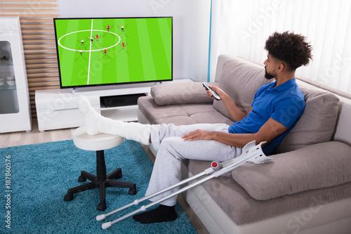 Fotobehang Voetbal Man With Broken Leg Watching Football Match On Television