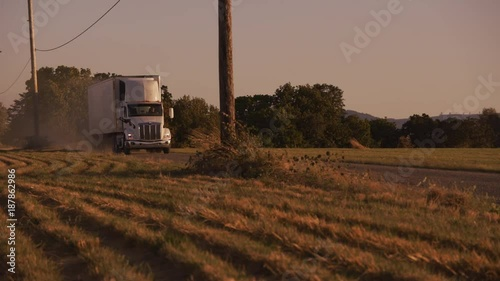 Semi truck driving down dusty road at sunset.  Fully released for commercial use.