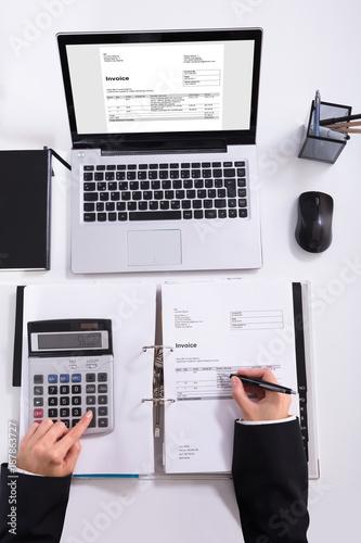 Businesswoman Hand Calculating Invoice Using Calculator - 187863727