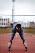 young sportsman makes exercises on a running track
