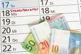 Ein Kalender mit einem Termin beim Steuerberater und viele Schweizer Franken Geldscheine