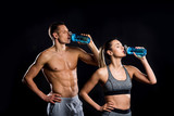 Athletic Young Couple In Sportswear Drinking From Bottles  On Black Wall Sticker