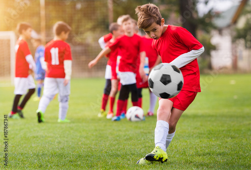 Foto Murales Boy kicking football on the sports field