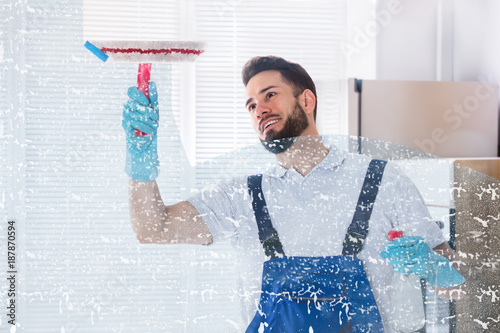 Foto Murales Janitor Cleaning Window With Squeegee