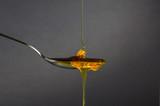 Honig tropft vom Löffel - 187871704