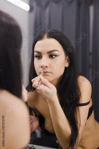 Young brunette doing herself makeup by the mirrow