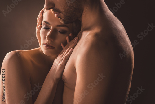 naked tender couple embracing with closed eyes, on brown