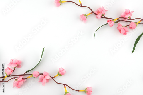 Fake pink flower branches on white background with copy space